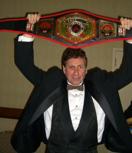 Frank Dux holding one of his many championship belts.