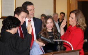 The new Niagara County District Attorney Caroline Wojtaszek is sworn in by Niagara County Judge Sara Sheldon as her husband Henry and son and daughter look on.