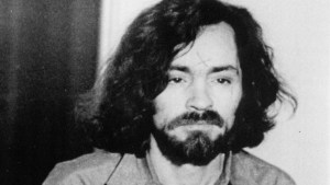 Charles Manson (right) being escorted to the courtroom by a sheriff's deputy (August 11, 1970)